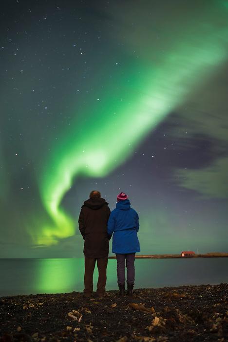 Couple watching the Northern Lights (Aurora Borealis), Reykjavik, Iceland